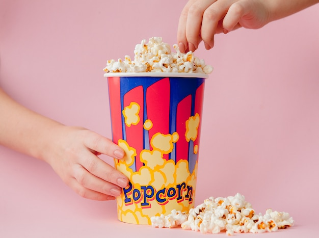 Hand takes a popcorn from a paper cup