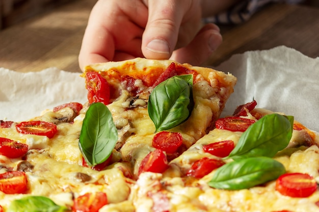 A hand takes a slice of homemade pizza close up
