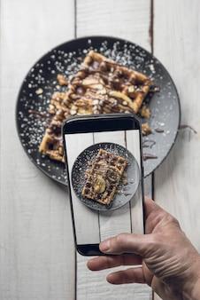 Рука сфотографировать вафли с смартфона