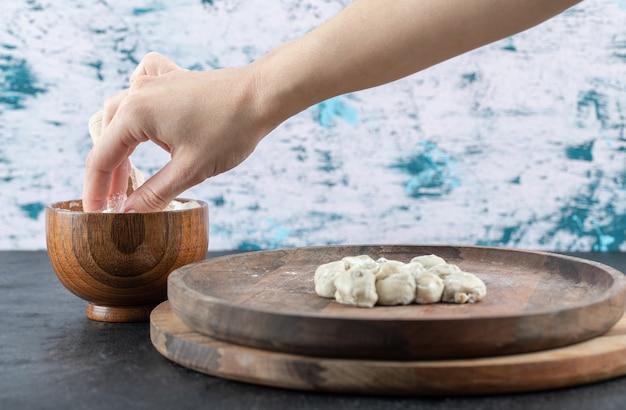 灰色の木製のボウルから小麦粉のピンチを取る手。