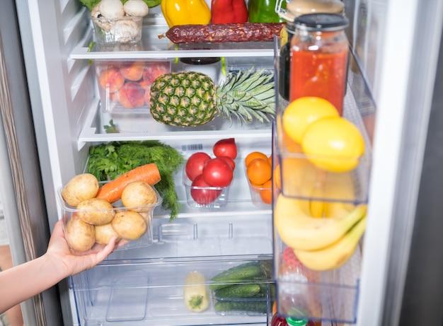冷蔵庫から野菜の入った容器を手に取る