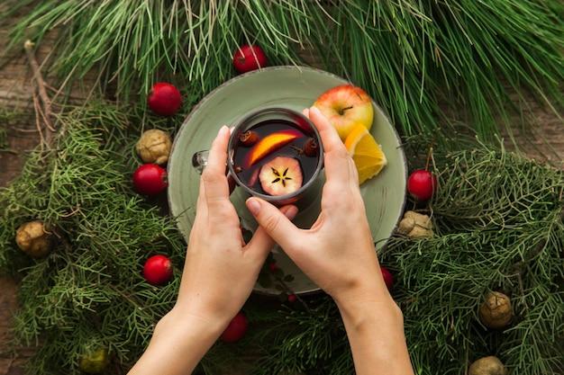 크리스마스를 위해 장식된 수제 mulled 와인과 함께 손을 잡는 컵