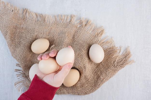 Рука берет яйца из пачки на куске ткани на мраморном столе.