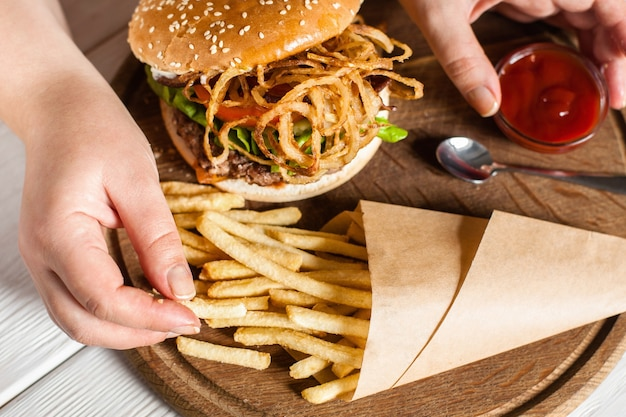 햄버거와 함께 쟁반에 종이 팩에서 감자 튀김을 복용하는 손