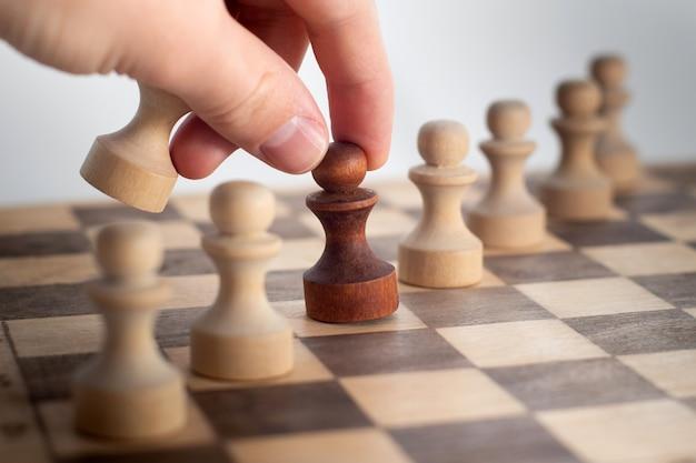 チェスゲームで彼の次の一歩を踏み出す手。チェス盤で暗いチェスの駒を動かす人間の手。