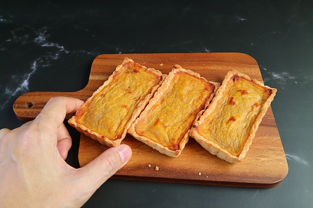 Hand taking a mouthwatering pumpkin tartlet from the wooden breadboard