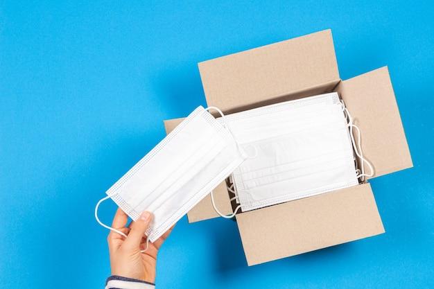 밝은 파란색에 의료 마스크를 많이 가진 열린 종이 상자에서 하나의 의료 마스크를 복용하는 손. 평면도