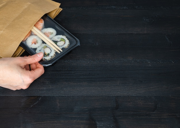 Hand taking out sushi tray from paper bag on black wooden background. copy space. food concept.