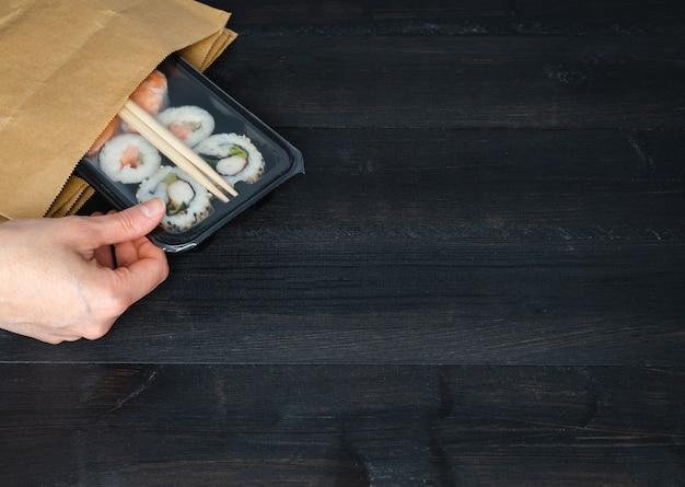 Рука, вынимая лоток для суши из бумажного пакета на черном деревянном фоне. скопируйте пространство. концепция питания.