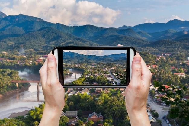 Рука фотографирует в точке зрения и пейзаже в луанг-прабанге, лаос.