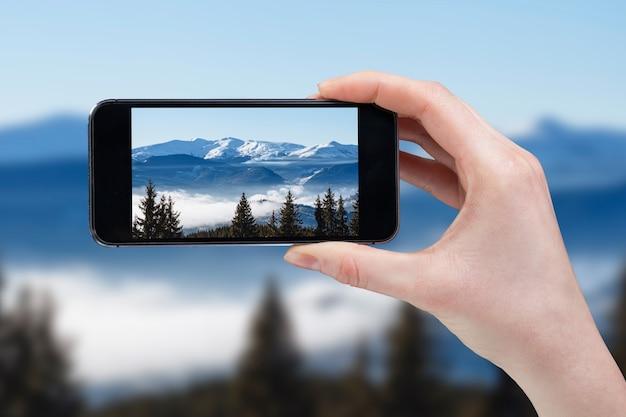 携帯電話で山頂を手で撮る