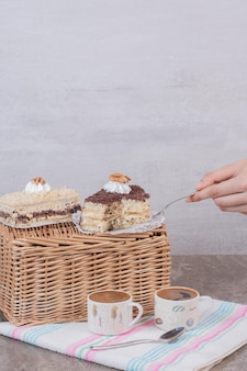 Hand taking a piece of cake on white table .