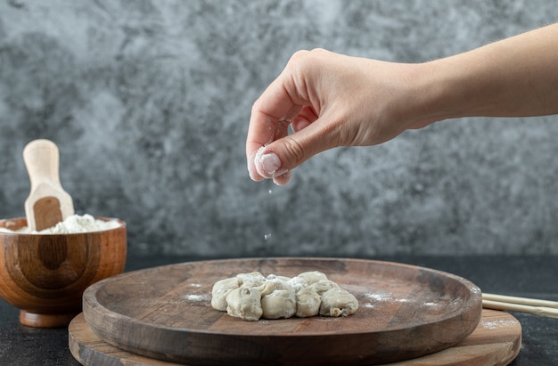 Hand taking a pinch of flour from a wooden bowl on a gray