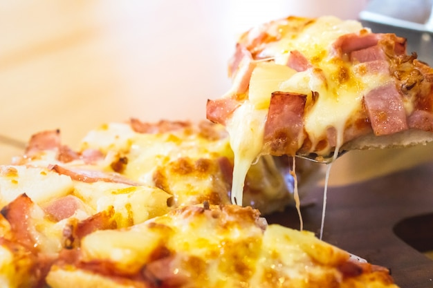 Hand taking pizza ham with melting cheese slice