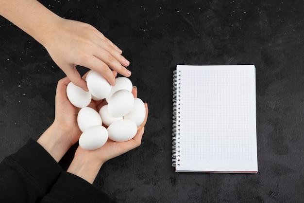 검은 배경에 여성 손에서 원시 흰 계란을 복용하는 손.