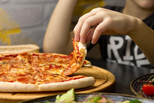 Рука, принимая кусок пиццы пепперони из круглого деревянного подноса