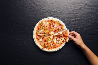 Hand taking slice of pizza