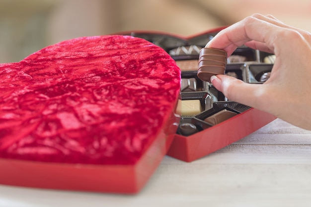 Hand taking a truffle of a heart shaped box of chocolates