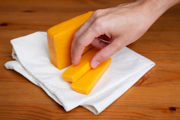 Рука с желтым сыром лежит на белой ткани