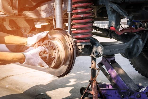 Hand technician wearing gloves, repairing car brake.
