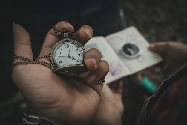 Hand that holds the clock and the background blurred pass sports and compass.