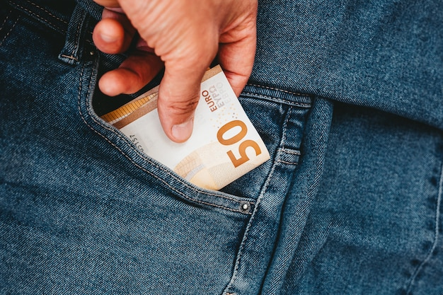 The hand that puts euro banknotes in a pocket of jeans