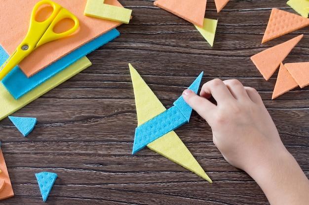 위의 그림 비행기 tangram 퍼즐 사각형 나무 테이블에서 수집 된 아이를 건네줍니다.