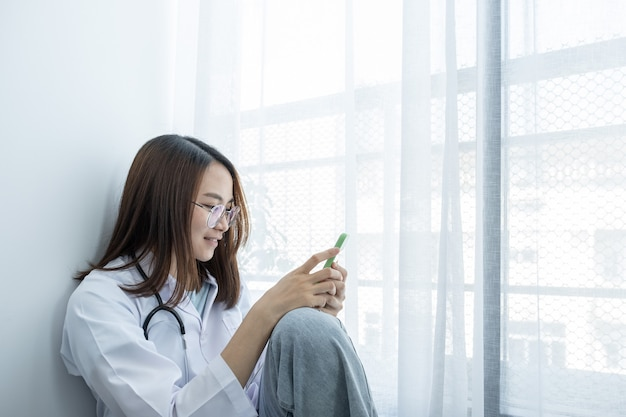 Рука, врач носит стетоскоп, сидит возле окна и пользуется смартфоном.