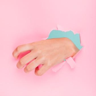 Hand through a paper hole
