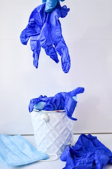 Рука выбрасывает использованные инфекционные маски и медицинские перчатки в мусорное ведро. коронавирусный мусор. covid-19 медицинские отходы. использованы средства индивидуальной защиты сиз. загрязнение пластиком после пандемии