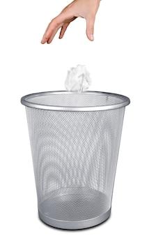 Рука выбрасывает бумагу в корзину для мусора, изолированную на белом