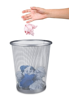 Hand throwing out paper into trash basket isolated on white