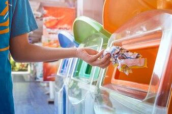 廃棄物をリサイクルビンに投げる手、環境保護の概念