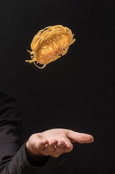 Рука подбрасывает макароны в воздух