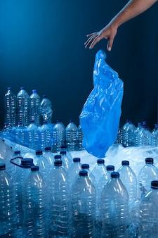 Рука бросает полиэтиленовый пакет в кучу пластика. концепция переработки пластика и экологии.