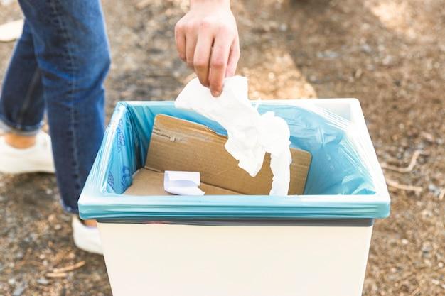 Рука бросает мусор в корзину на открытом воздухе