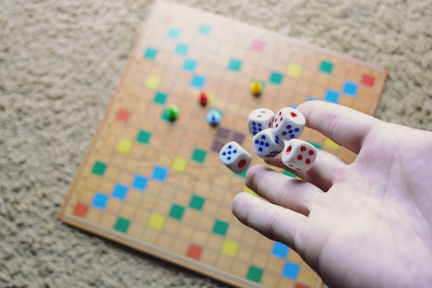 Hand throwing white dice background colorful blurred board game