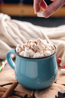 Hand throws marshmallow in a mug of hot chocolate.