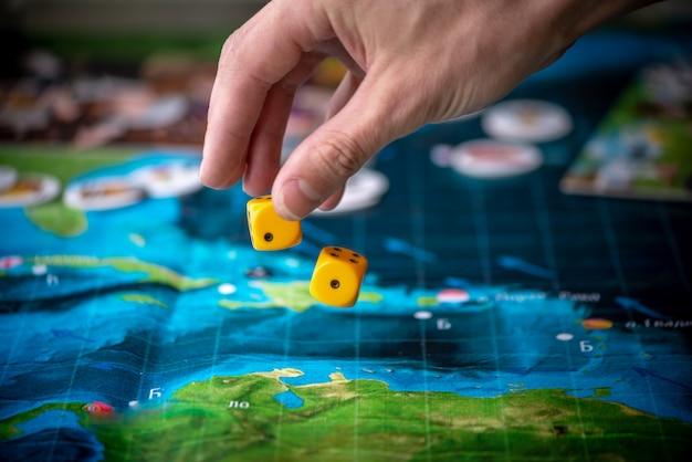 Рука бросает два желтых кубика на игровое поле. игровые моменты в динамике. удачи и азарта. стратегия настольных игр