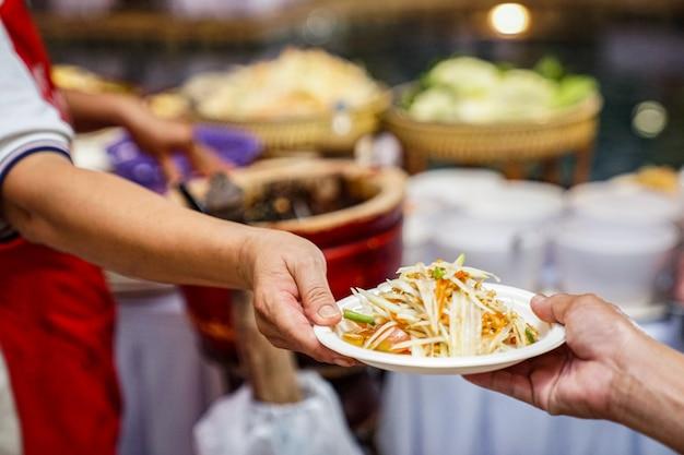 世界で有名な地元の伝統的なユニークなサラダを手にしたソムタム(スパイシーなタイのパパイヤサラダ)。