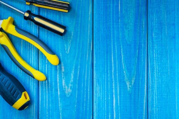 宿題のための青い木製の背景に手工具。家事用または錠前屋用のキット。