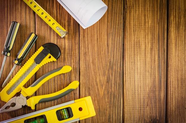 Ручной инструмент на темной деревянной стене с рекламным пространством