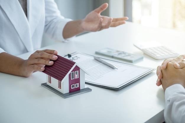 Модель дома касания руки агент по недвижимости объясняет деловой договор