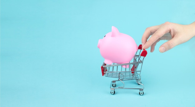 Hand touch mini shopping trolley with piggy bank on blue background. saving money for sales of the year, black friday concept.