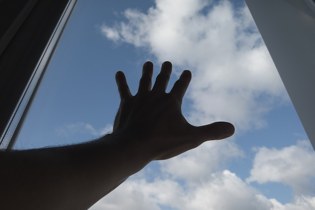 A hand touched the window pane. the sky in the background