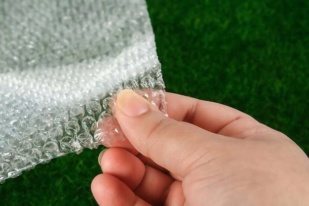 The hand touches bubble wrap. the concept of touch, tactility, feelings.