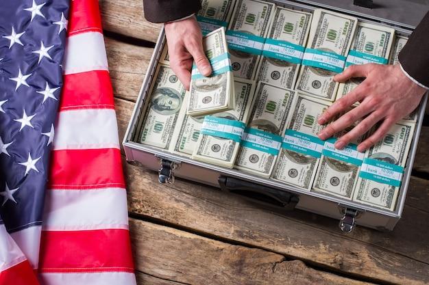 Рука касается долларов в чемодане. флаг сша, лежащий рядом с наличными деньгами. лучше спрячь это подальше. жадность и страх.