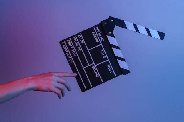 Рука касается доски с хлопушкой пленки в сине-красном неоновом свете. киноиндустрия, развлечения. концепт-арт, минимализм