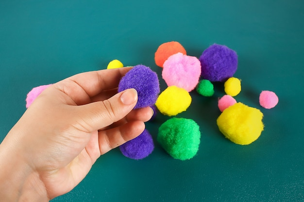 Hand touches soft woolen pompom. the concept of touch, tactility, feelings.