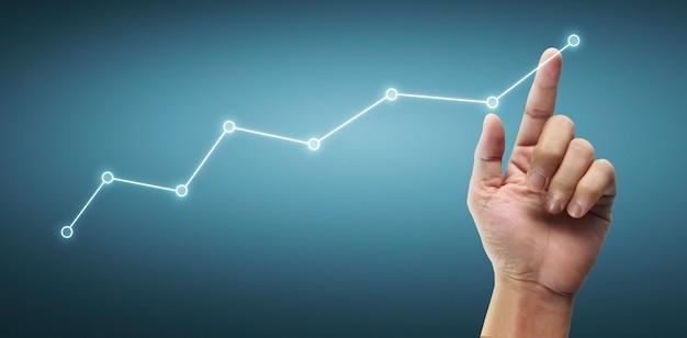 재무 지표 및 회계 시장 경제 분석 차트의 그래프를 만지는 손